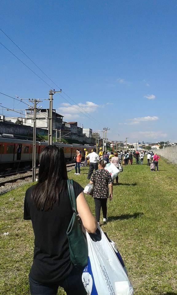 Usuários caminhando nos trilhos da linha 11. Foto: Adriana Oliveira